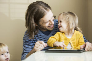 Father (30s) playing with daughter (2 years) who has down syndrome. Using digital tablet.